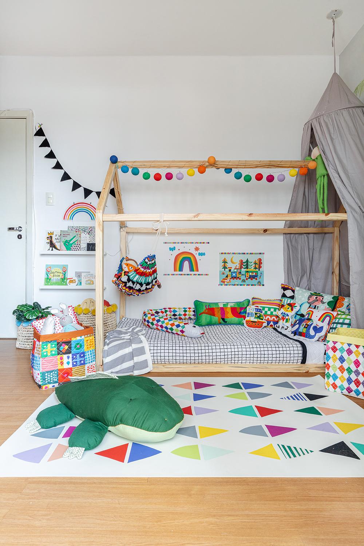 quarto infantil com cama casinha e tapete estampado colorido
