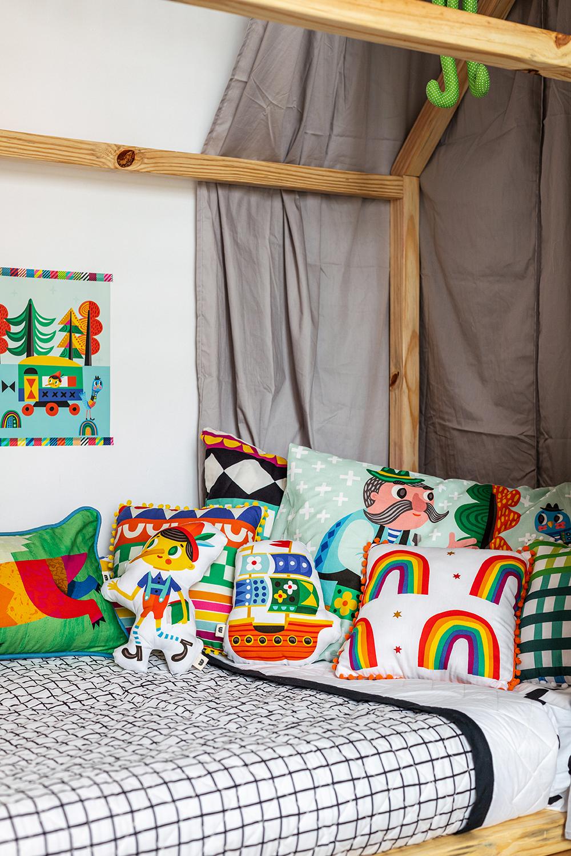 cama infantil com colcha matelassada e almofadas coloridas