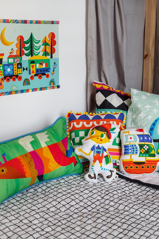 cama infantil com colcha matelassada e almofadas