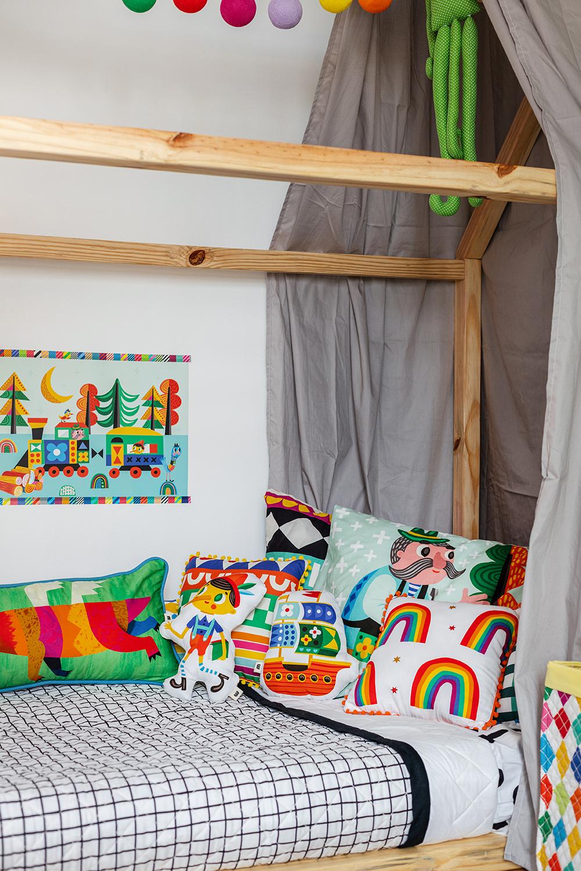 cama infantil com colcha matelassada e almofadas estampadas
