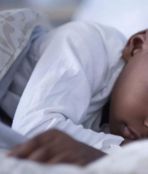 criança coberta dormindo na cama